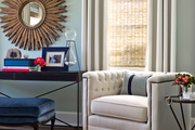This corner features a console table, a comfy chair, and a statement mirror.