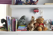 Stuffed animals and book atop white shelves.