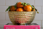Gold fruit bowl atop stack of books and marble countertop.