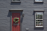 A wreath hung on a brick-red door