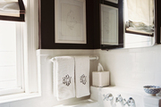 Brown walls and white tile with monogrammed hand towels in a bathroom