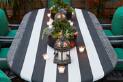 An outdoor table with a runner, succulents, Moroccan lanterns, tea lights, and chairs with outdoor cushions under a striped canopy
