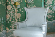 An upholstered armchair with nailhead trim in front of a chinoiserie panel