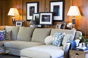 A sectional sofa backed by framed photographs