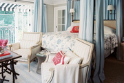 A pair of armchairs at the foot of a canopy bed outfitted with blue curtains