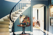 A curved staircase in a blue hallway