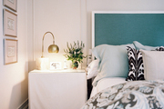 A skirted bedside table paired with a blue upholstered bed