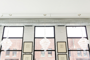 A trio of bubble chandeliers against tall loft-like windows