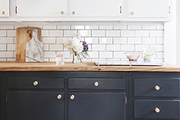 Butcher block countertops atop dark-painted cabinets with white cabinetry above.
