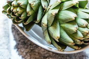 A detail of artichokes in a white bowl.