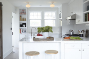 White and grey kitchen with marble countertops and modern stools