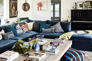 A living room with an oversized velvet sofa, mixed throw pillows and a rough-hewn coffee table