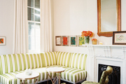 A striped banquette with a pair of upholstered chairs beside a fireplace