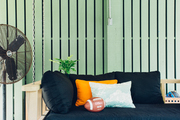 A hanging bench in front of a painted green wall.