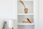A white shelving unit holds decorative pieces.
