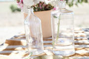 Flowers are arranged in glass vases on an outdoor table.