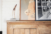 Art layered atop a wooden mantel
