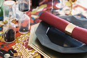 A festive table setting with gold flatware and a colorful runner
