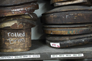 Hat molds organized neatly on a shelf of a  millinery