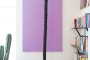 A hanging black rope in front of a purple painting.