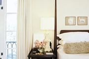 A wooden four-poster bed next to a tiered black bedside table