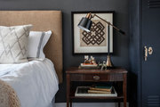 A bedside table holds a black-and-brass library-style lamp
