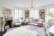 Large white living room with vintage furniture and multiple book shelfs.