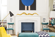 A Sputnik chandelier, a bench with a chevron throw, an armchair and a glass-topped table
