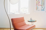 A floor lamp behind an orange midcentury chair