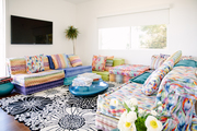 A living room with a colorful printed couch and a black and white retro printed area rug.