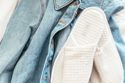 A detail of a denim shirt with white slippers.