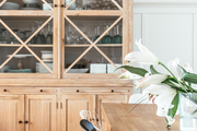 A large cabinet stores glassware by the table.