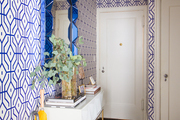 Vibrant patterned walls and white moulding surround this room.