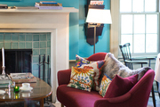 A fuchsia settee nearby a glass-tiled fireplace