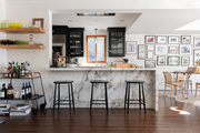 Marble kitchen counters with black stools, wooden shelves, and a bar cart.