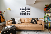 Leather sofa and black and white wall art in eclectic living space.