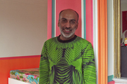 Dressed in graphic green and black, designer Manish Arora leans against a door in his apartment