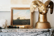 Framed art and a brass ram head atop a mantel