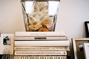 A lantern filled with shells and white coral atop a stack of books