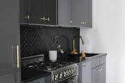 Contemporary kitchen with black cabinets and gold hardware