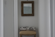 Framed mirror above small stool in white hallway.