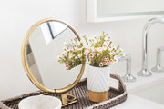 Details of a contemporary white bathroom with gold vanity mirror and flowers in a vase.