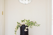 A tall vase of flowering branches below a candle sconce