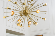 A Sputnik chandelier and framed art set off by white walls and geometric molding