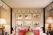 A grouping of floral prints hung below the canopy of a four-poster bed