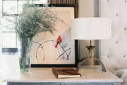 A marble-topped bedside table decorated with art and a brass lamp