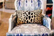 An ikat-upholstered chair with a leopard-print pillow