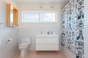 A contemporary bathroom with white walls and a blue and white shower curtain.