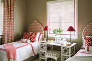 A guest room with batik-printed upholstered beds and sheer window treatments