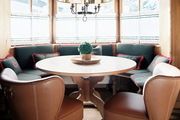 A dining space with leather chairs and a banquette set in a bay window